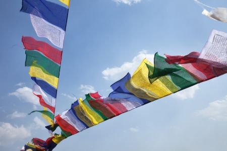 Buddhist Tibetan prayer flags flying in the wind against blue sky Stock Photo