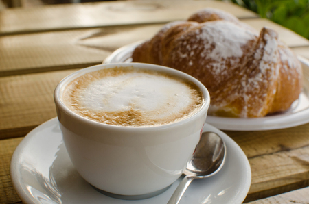 breackfast: The cup of cappuccino with croissant in the background - the tipical italian breackfast. Stock Photo