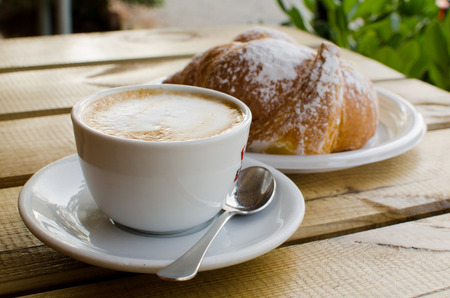 breackfast: The cup of cappuccino with croissant in the background - tipical italian breackfast. Stock Photo