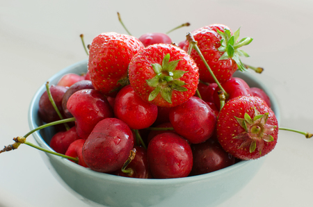 Cherry and strawberries on the plate  on the white background
