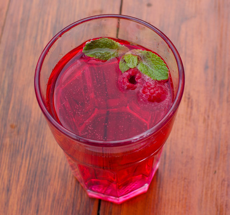 Lemonade with raspberries and mint on the wooden table