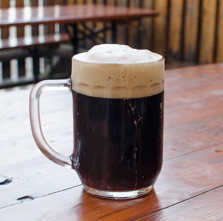 The mug of beer with foam on the table Stock Photo