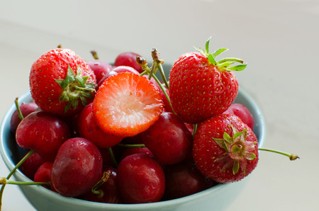 Cherry and strawberry on the plate  on the white background