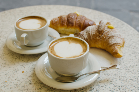 breackfast: Two cups of cappuccino with two croissants - the tipical italian breackfast.