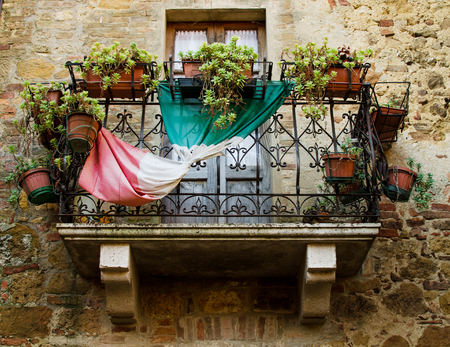 A balcony with flowers and italian flag in Pienza, Italy