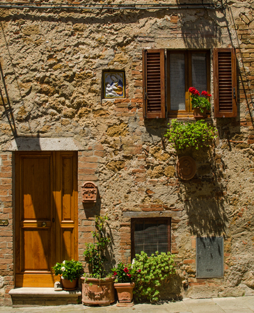 A house with window and door with flowers of Pienza, Italy Stock Photo