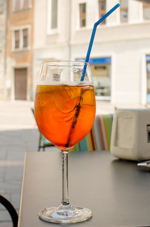 The glass of aperol spritz with straw