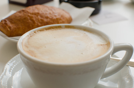 The cup of cappuccino with croissant in the background.