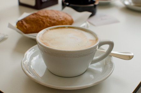 The cup of cappuccino with croissant in the background Stock Photo