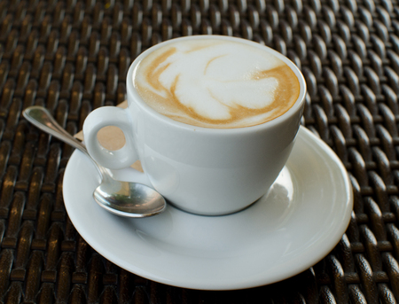 The cup of cappuccino on the wicker table Stock Photo