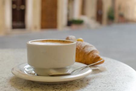capuchino: La taza de capuchino con croissant en la calle el modo de fondo
