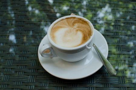 cappuccino cup: The cup of cappuccino on the glass surface