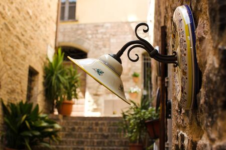 Ceramic street lamp  with old street of Spello how background, Italy