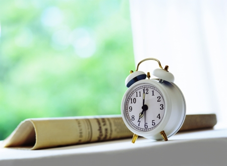 newspaper and alarm clock