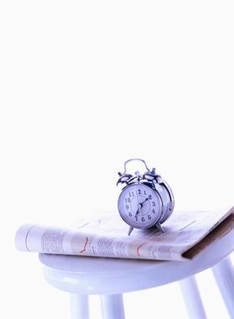 目覚まし時計と新聞 写真素材
