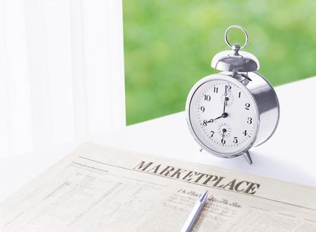 alarm clock and newspaper Фото со стока