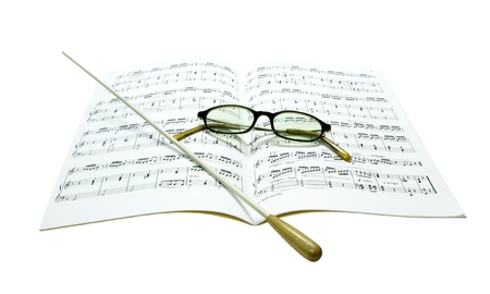 Baton and glasses on music score isolate on white background