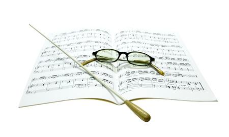 music score: Baton and glasses on music score isolate on white background