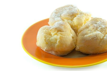 Three cream puffs on orange plate closeup on white background Stock Photo - 22125504