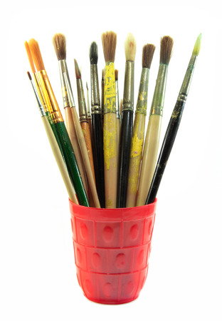 Paint brushes set in the red cup on white background photo