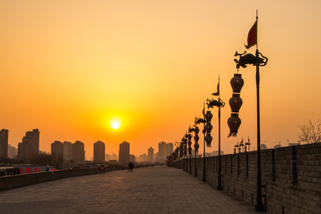 historic sites: XIAN, CHINA - MARCH 13 2016: Silhouette of people walks  at City Wall of Xian in the evening. March 13, 2016 a famous Historic Sites in Xian, Shaanxi, China. Editorial