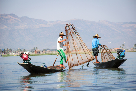 INLE LAKE, MYANMAR - JANUARY 20, 2017: Burmese fisherman catching fish in Inle lake, Myanmar by a handmade net on January 20, 2017. Traditional way of fishing in Myanmar
