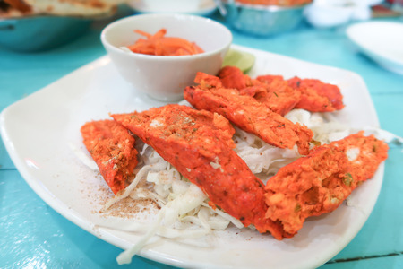 Chicken tikka kabab, Indian food with salad on wood table Stock Photo