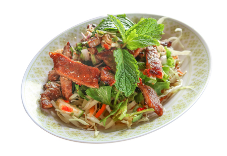Sliced grilled beef salad, Thai food in green dish on white background