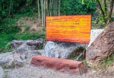 KANCHANABURI PROVINCE, THAILAND - APRIL 16, 2019: Sign name of Jokkradin waterfall in Thai language, Kanchanaburi, Thailand