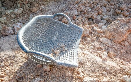 Clam-shell shaped basket on soil pile Stock Photo
