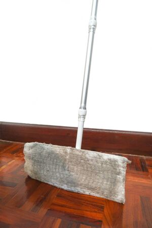 Dirty mop with dust and dirt on parquet floor