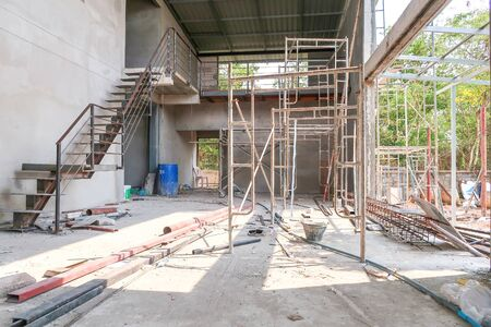 The two-story house under the construction has a steel ladder, scaffold and steel bar on the ground.