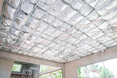 Home under construction install heat insulate ceiling in the form of foil.