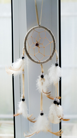 Dreamcatcher hanging on the window. White and light brown