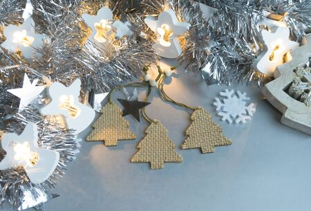 Christmas and New Year background. Snowflake, wooden Christmas trees, tinsel, stars and a luminous garland of angels on a silver background.