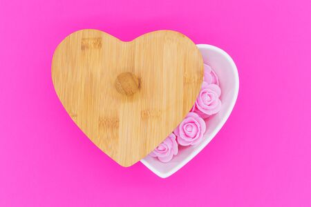 Pink flowers in a heart-shaped casket with wooden lid against a pink background. Valentines day background. Mothers Day, March 8th background. Flat lay, top view