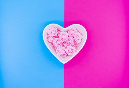 Pink flowers in a heart-shaped casket against on bright pink and bright blue background. Valentines day background. Mothers Day, March 8th background.