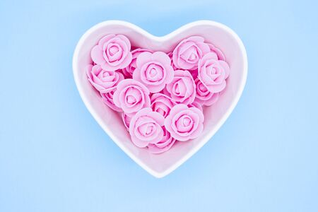 Pink flowers in a heart-shaped casket against a light blue background. Valentines day background.