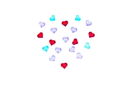 Valentines Day holiday celebration concept. Red, blue and lilac glass hearts laid out in the shape of a heart on a white background. A big heart is made up of little hearts.
