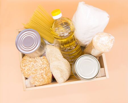 Wooden donation box with food: canned food, pasta, peas, millet, sugar, vegetable oil, cookies on an orange background. Top view. Food stock for quarantine isolation period.
