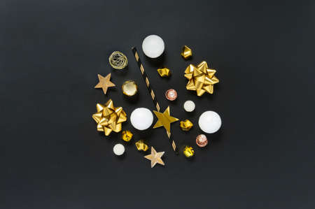 Festive black, white and gold objects in the shape of a circle on a black background, top view. Christmas, winter holiday, party, new year concept. Flat lay