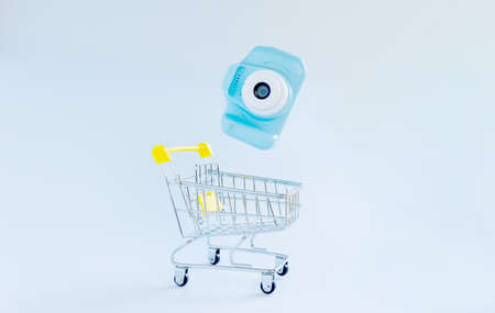 Blue photocamera falling in shopping cart on white backround. Electronics and photographic equipment shopping concept Фото со стока