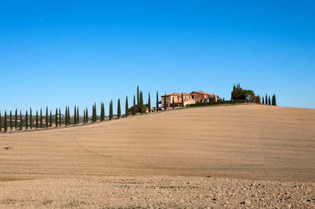 Villa in Tuscany with cypress road or alley in autumn, Valley of Val Dorcha, Italy. Stock Photo