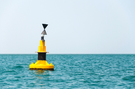 floating yellow buoy on blue sea Stock Photo