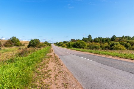 Asphalt road through green hills and trees. Panoramic view of the road among the forest. The asphalt road in the summer.