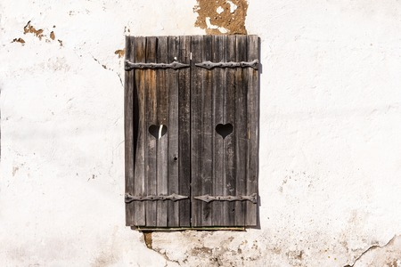 Wooden grey shutters with heart on an old wall. Old wooden windows frame on stone wall. White background