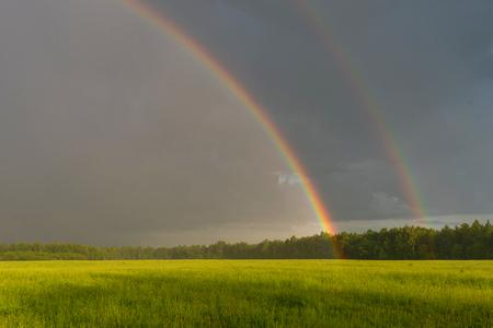 Schöne Landschaft mit einem dramatischen Himmel und einem doppelten Regenbogen. Grünes Feld unter bewölktem Himmel mit doppeltem Regenbogen.