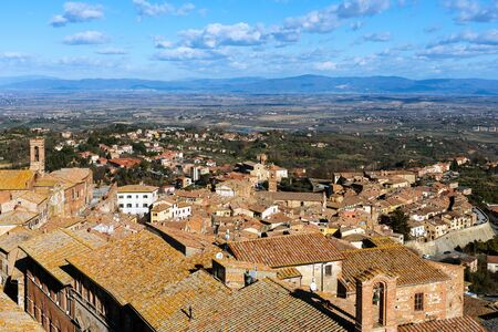 Picturesque aerial view of the medieval town Montepulciano in Tuscany, Italy. Aerial view of stone houses and green valley with vineyards and cypress trees in winter.