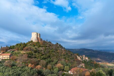 Amazing landscape of the Tuscan countryside with the medieval fortress Rocca of Tentennano on the hill in winter. Tuscany, Italy.
