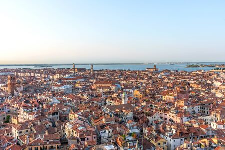 Picturesque panoramic view of Venice, Italy. Aerial scenery view with red roofs of houses. Top view from Campanile di San Marco at sunset
